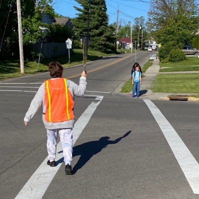Crossing guard helping student across the street